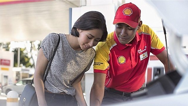 Shell station employee demonstrating to a customer